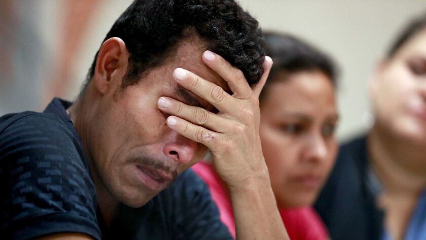 Melvin, foreground, and Iris, both from Honduras, listen as they hear other immigrants tell of their