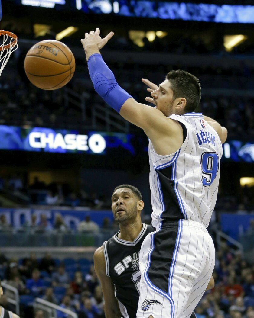 Orlando Magic's Nikola Vucevic (9) loses control of the ball as he goes to the basket in front of San Antonio Spurs' Tim Duncan, left, during the first half of an NBA basketball game, Wednesday, Feb. 10, 2016, in Orlando, Fla. (AP Photo/John Raoux)