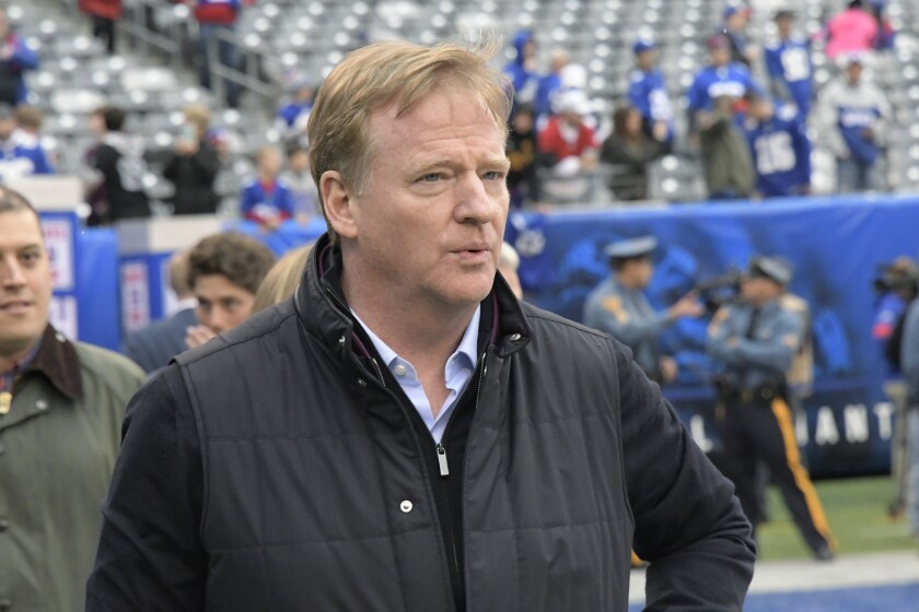 NFL Commissioner Roger Goodell walks on the field before a game.
