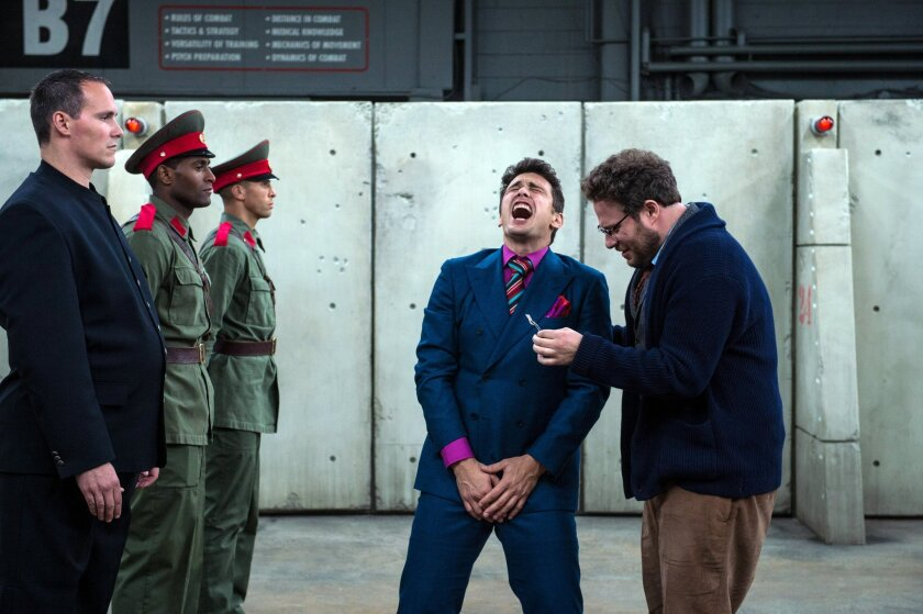 "James Franco, center, and Seth Rogen, right, in a scene from ""The Interview."""