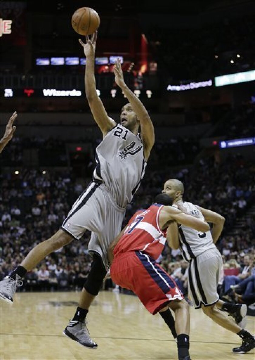 San Antonio Spurs' Tim Duncan (21) is hit by Washington Wizards' Garrett Temple (17) as he shoots during the first half of an NBA basketball game on Saturday, Feb. 2, 2013, in San Antonio. (AP Photo/Eric Gay)