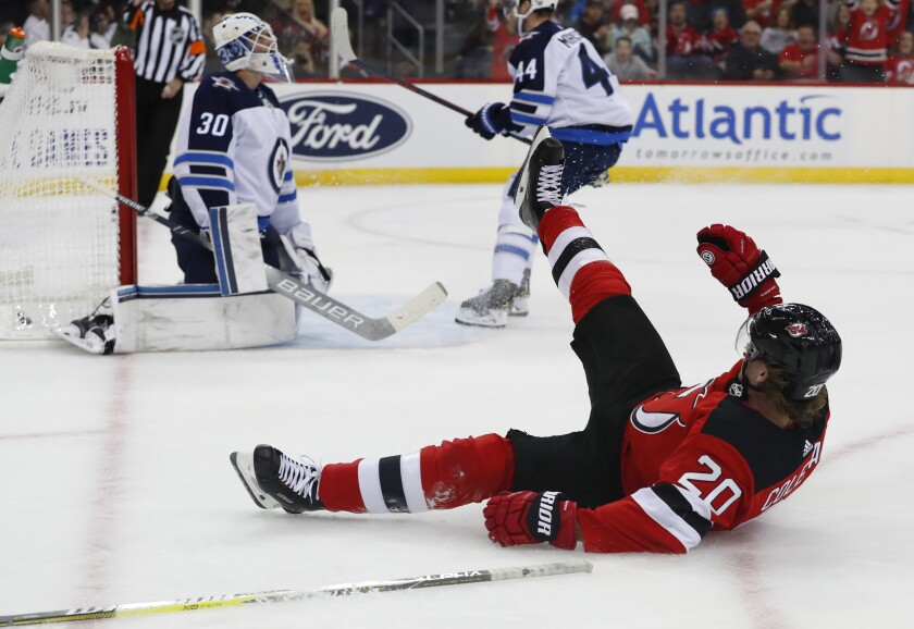 Winnipeg Jets goaltender Laurent Brossoit (30) reacts after a goal scored by New Jersey Devils center Blake Coleman (20) during the second period of an NHL hockey game Friday, Oct. 4, 2019, in Newark, N.J. (AP Photo/Noah K. Murray)