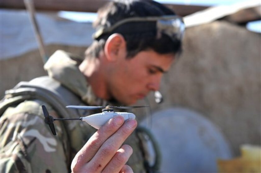 Undated image released by the British Army Monday Feb 4 2013 of Sergeant Scott Weaver, of The Queens Royal Lancers launching a newly issued Black Hornet miniature surveillance helicopter  during an operation in Afghanistan.  The Scandinavian-designed Black Hornet Nano weighs as little as 16 grams (