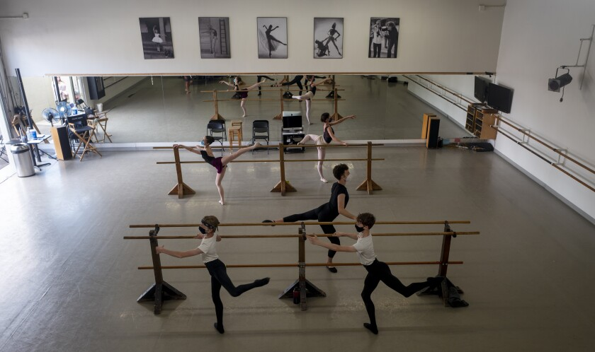 Five young dancers wearing masks rehearse at a barre in a dance class.
