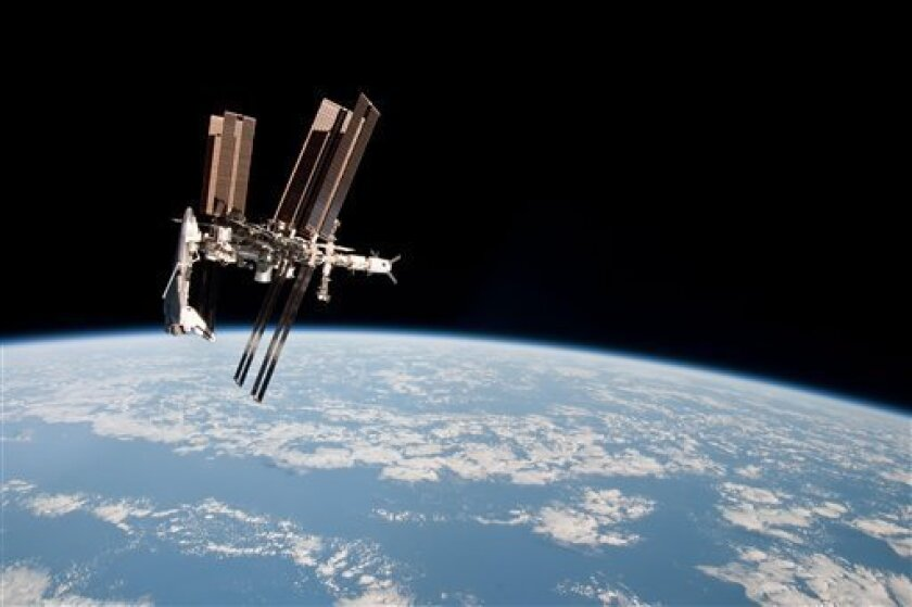 This May 23, 2011 photo made by Expedition 27 crew member Paolo Nespoli from the Soyuz TMA-20 following its undocking and released by NASA shows the International Space Station and the docked space shuttle Endeavour, left, at an altitude of approximately 220 miles. A Soyuz capsule had never headed for home while a shuttle was parked at the space station, providing a rare opportunity for the photo session. (AP Photo/NASA, Paolo Nespoli)