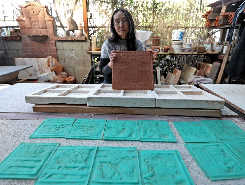 Pasadena tile artist Cha-Rie Tang shows a clay negative she made to recreate an Arts and Crafts-era tile fireplace made by Ernest Batchelder, which sits in a building owned by La Cañada Unified School District slated for demolition.