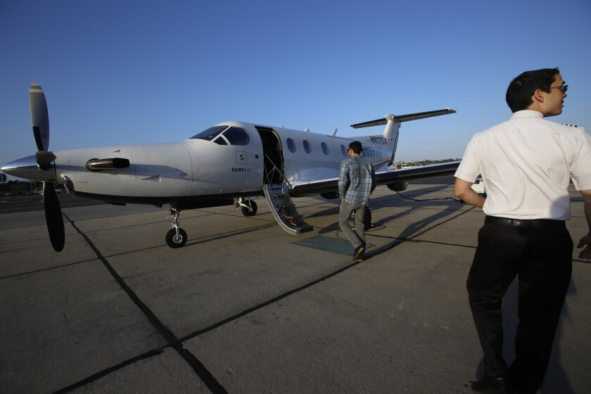 Captain Chris Pimentel, right, waits for passengers to board the SurfAir airplane at the Hawthorne Municipal Airport in Hawthorne last year. SurfAir is an all-you-can-fly membership airline.