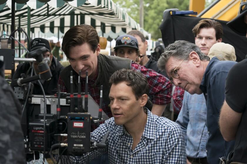 Three men huddle around equipment on the set of a movie