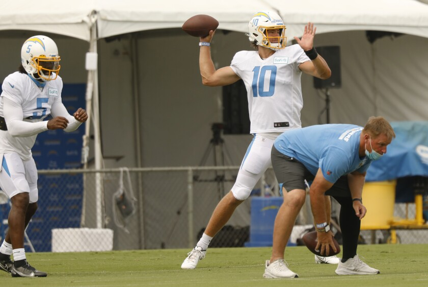 Chargers quarterbacks Tyrod Taylor (left) and Justin Herbert take practice snaps.