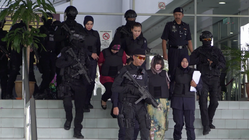 """Doan Thi Huong and Siti Aisyah are escorted out of the courthouse by armed guards in the documentary """"Assassins."""""""