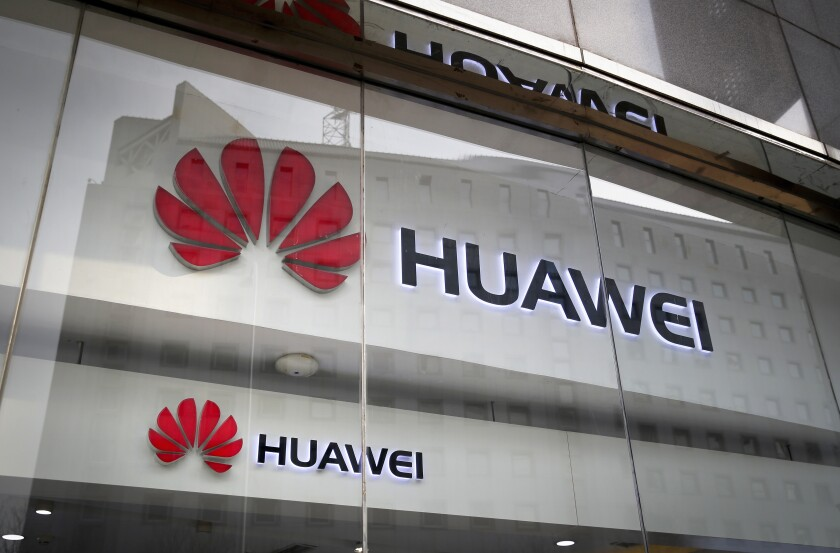 FILE - In this Jan. 29, 2019, file photo, logos of Huawei are displayed at its retail shop window with the reflection of the Ministry of Foreign Affairs office in Beijing. A committee of lawmakers on Thursday Oct. 8, 2020, is urging the British government to consider banning Chinese technology giant Huawei from the country's next-generation mobile phone networks two years earlier than planned. (AP Photo/Andy Wong, File)