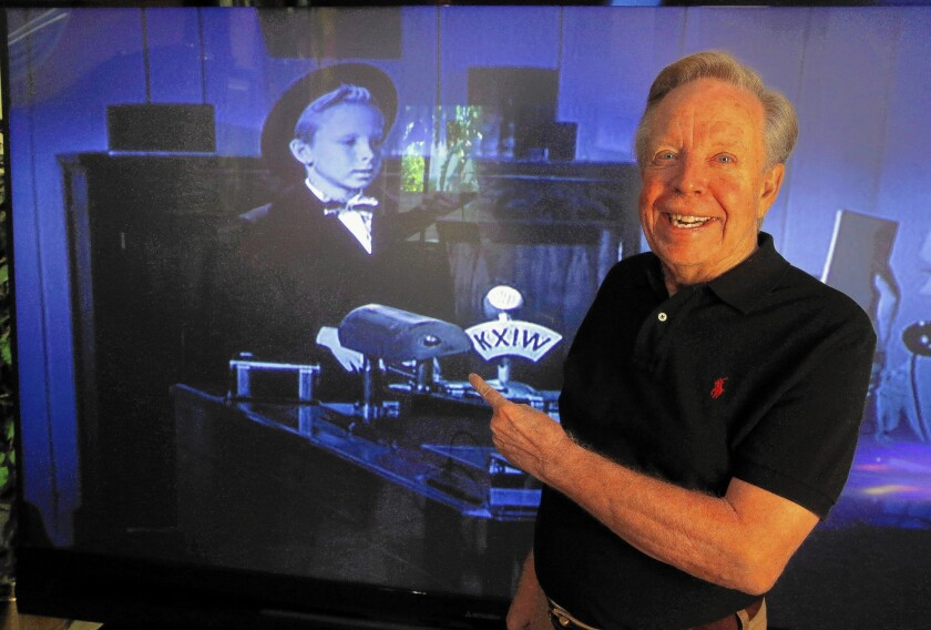 """Tommy Ivo of Burbank, a onetime child actor, became such a passionate drag racer that he calculates he owned 36 cars over the years. Above, he points to an image of him in the 1949 movie """"Feudin' Rhythm."""""""