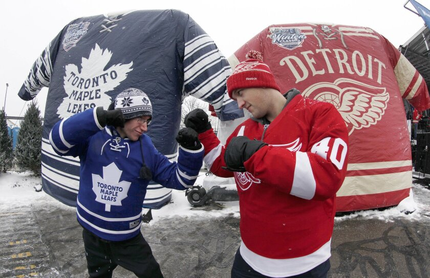 Nathan Dunville, of Halifax, Nova Scotia, left, and Adam Boutilier, of Cole Harbour, Nova Scotia, pose for family photographs at the NHL Winter Classic hockey game at Michigan Stadium in Ann Arbor, Mich., Wednesday, Jan, 1. 2014, where the Detroit Red Wings play the Toronto Maple Leafs. (AP Photo/P