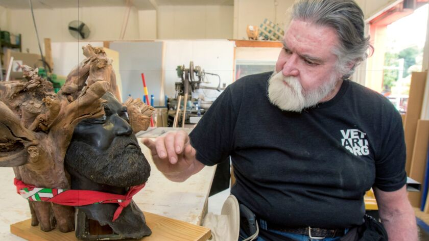 Veterans Art Project student Mick McCamm points out a detail in his wood-and-metal self-portrait sculpture, which will serve as the urn for his ashes when he dies.