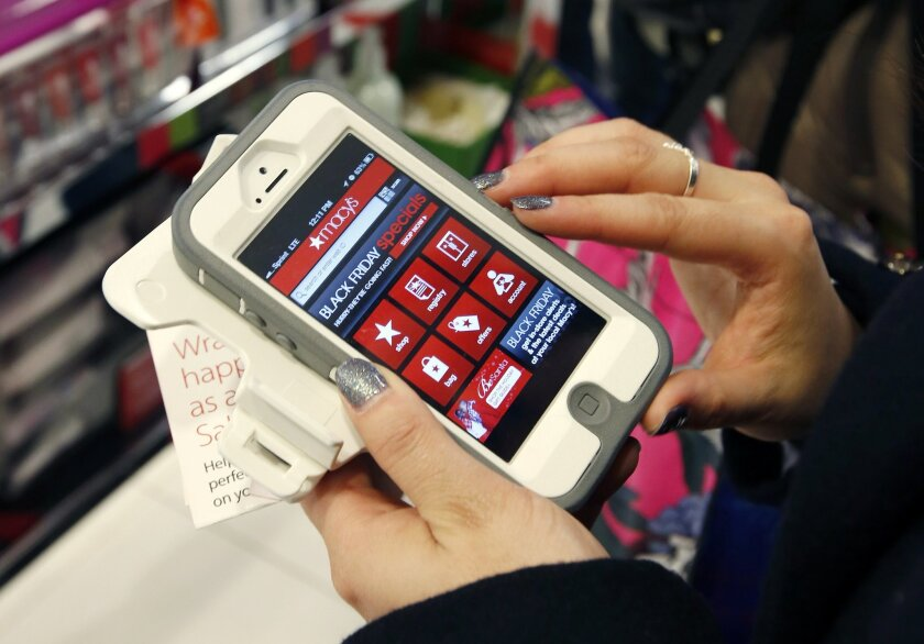 FILE - In this Friday, Nov. 23, 2012, file photo, Tashalee Rodriguez, of Boston, uses a smartphone app while shopping at Macy's in downtown Boston. For the first time, analysts predict more than half of online traffic to retailer sites will come from smartphones than desktops during the busy Black Friday holiday shopping weekend. And though it's still a small fraction of online revenue, mobile sales are jumping too. Larger phone sizes, improved retailer apps, more online deals and shoppers' increasing comfort with shopping online are driving the trend. (AP Photo/Michael Dwyer, File)
