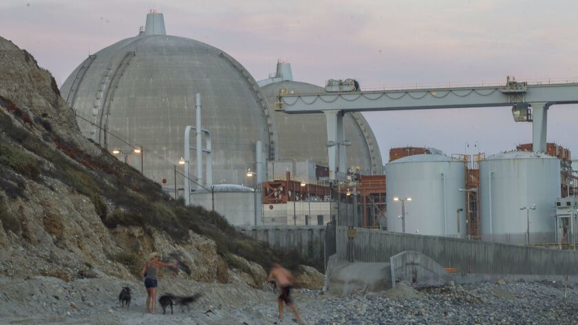 A man and woman relax at the beach next to the San Onofre Nuclear Generating Station in an August 2018 file photo.