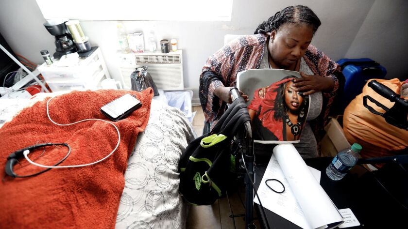 Natalie Purnell looks at a picture of her daughter inside her room at a former motel being used to house homeless women and children. She landed a shared room in the Figueroa Street building a year ago.