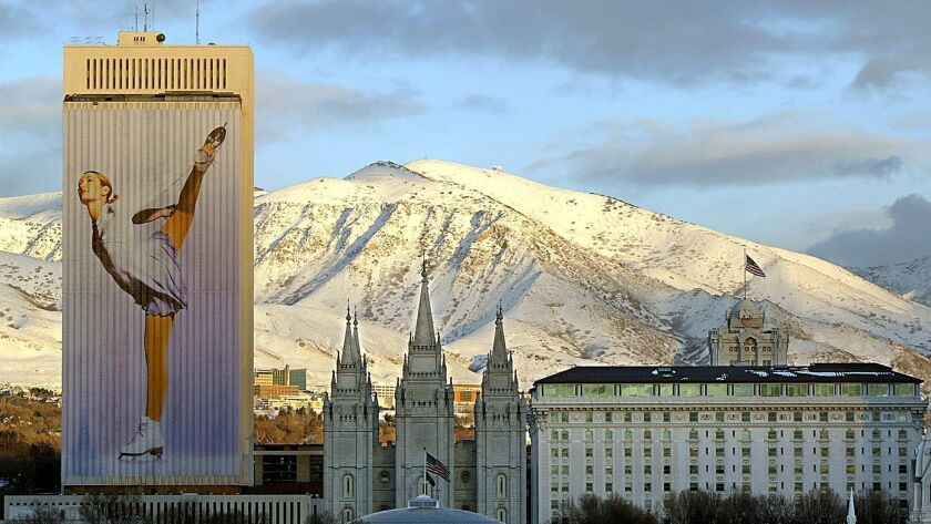 In this file photo taken on January 22, 2002 Downtown Salt Lake City is bathed in the evening sunlight as an Olympic sports banner drapes the 26 story Mormon church office building with the Mormon temple in the center.