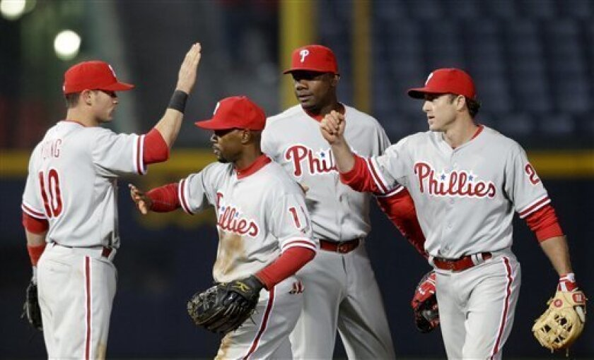 Philadelphia Phillies' Michael Young, from left, Jimmy Rollins, Ryan Howard, and Chase Utley, high-five one another after the Phillies beat the Atlanta Braves 2-0 in a baseball game, Thursday, April 4, 2013, in Atlanta. (AP Photo/David Goldman)