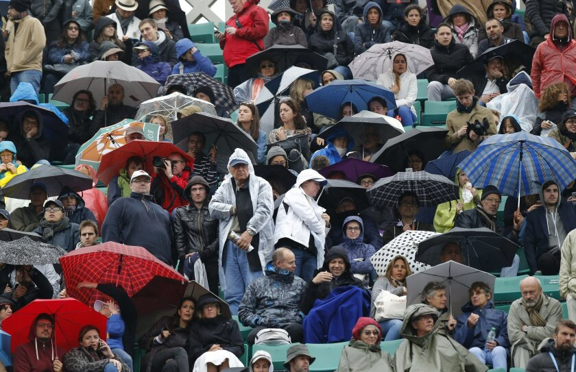 Spectators take cover under umbrellas as Serbia's Novak Djokovic plays his quarterfinal match of the French Open tennis tournament against Tomas Berdych of the Czech Republic at the Roland Garros stadium in Paris, France, Thursday, June 2, 2016. (AP Photo/Michel Euler)