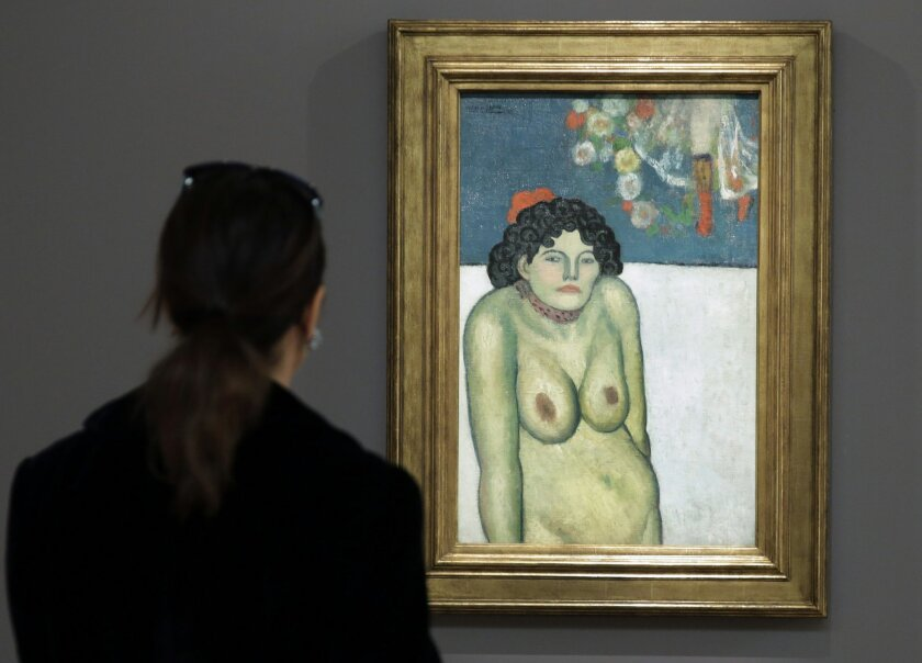 """FILE - This Oct. 30, 2015 file photo shows """"The Nightclub Singer,"""" a 1901 painting by Picasso from his Blue Period, at Sotheby's in New York. The work features a second picture on the reverse side depicting Picasso's art dealer, Pere Manach. The piece is estimated to fetch $60 million on Thursday n"""