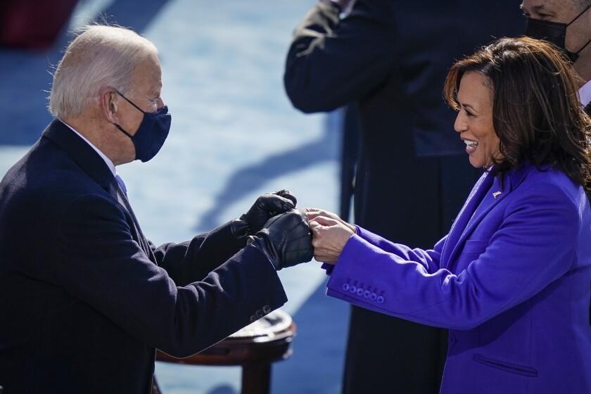 U.S. President-elect Joe Biden fist bumps newly sworn-in Vice President Kamala Harris.
