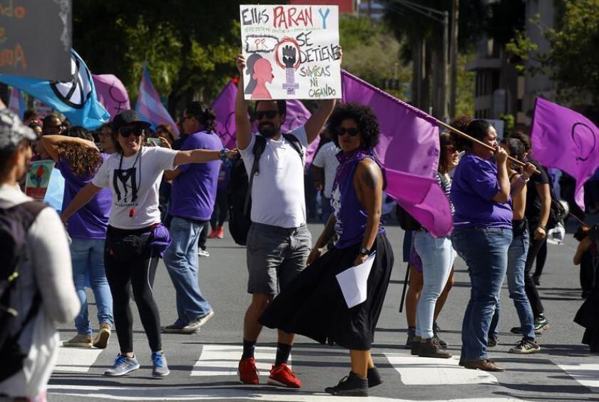 """Un hombre sostiene una pancarta que dice """"Ellas paran y P.R. se detiene"""" en solidaridad con las mujeres en la conmemoración del Día Internacional de la Mujer en San Juan, Puerto Rico. EFE/Archivo"""