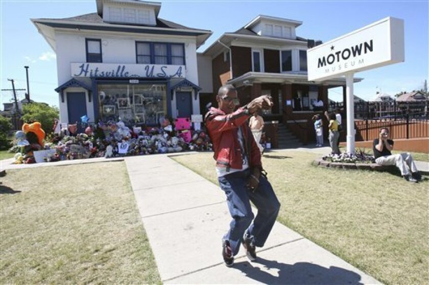 Tyuawn Brown, a 15-year Michael Jackson impersonator, dances in front of Hitsville U.S.A., Tuesday, July 7, 2009, where the pop megastar's recording career began 40 years ago, in Detroit. People have visited the historic building daily following the 50-year-old Jackson's death to pay their respects to the international icon. (AP Photo/Carlos Osorio)