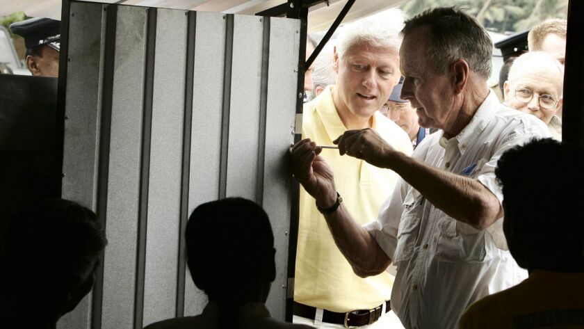 George H.W. Bush puts the final screw in a temporary home during a February 2005 visit that included Bill Clinton, center, to displaced tsunami victims in Weligama, Sri Lanka.