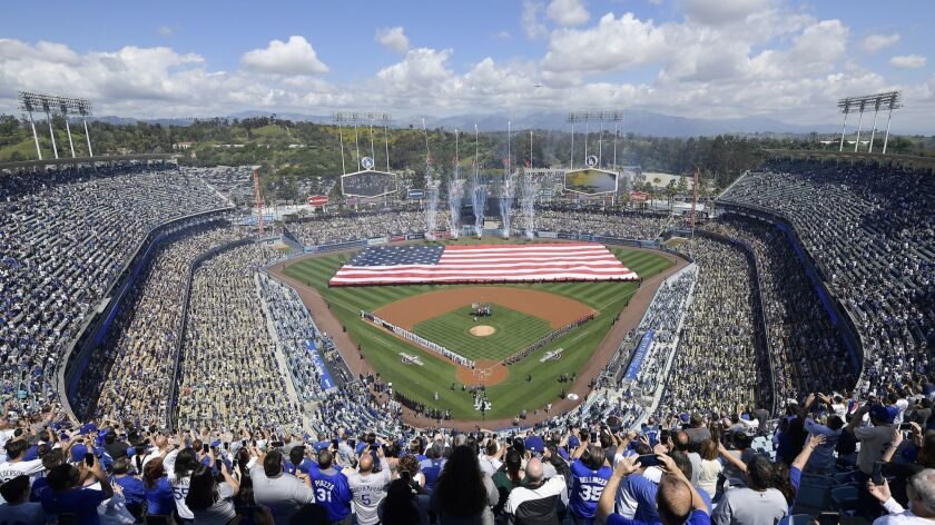 Fans stand for the national anthem before the opening day baseball game between the Los Angeles Dodg