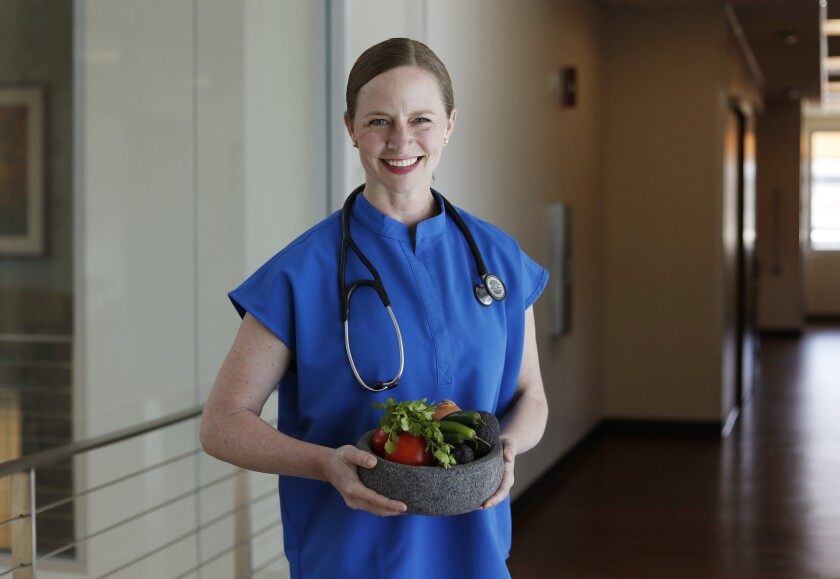 Dr. Sabrina Falquier Montgrain is a doctor of internal medicine with Sharp Rees-Stealy Medical Group and is certified in culinary medicine, providing nutritional education and cooking demonstrations in her volunteer work. She is shown here with a molcajete full of salsa-making ingredients.