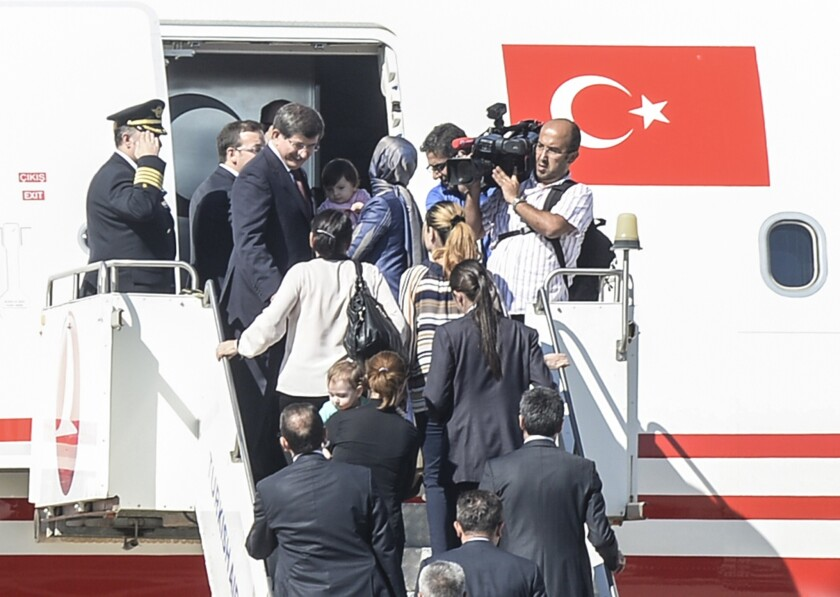 Turkish Prime Minister Ahmet Davutoglu, top, boards his plane with freed hostages at an airport in the southern Turkish city of Sanliurfa near the Syrian border.