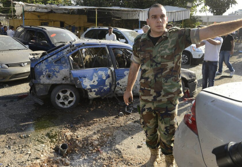 A Lebanese army officer stands next to a damaged car as he asks journalists to step back from the scene where a rocket struck a used car lot at the Mar Mikhael district of south Beirut on Sunday.