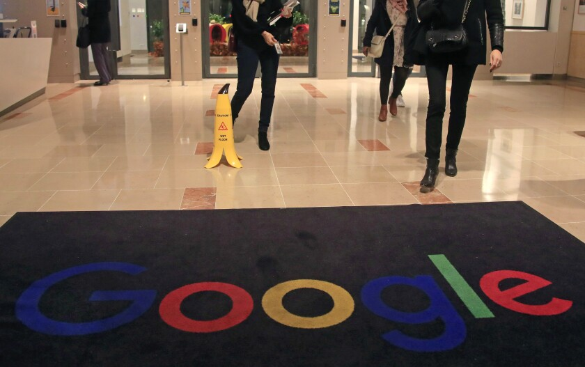 FILE - In this file photo dated Nov. 18, 2019, Google employees walk out of Google France building in Paris. France's competition regulator said Tuesday, July 13, 2021 it fined Google 500 million euros ($592 million) for failing to negotiate in good faith with French publishers in a dispute over payments for their news. (AP Photo/Michel Euler, File)