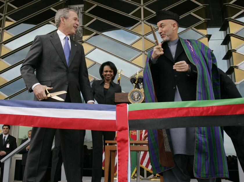 """FILE - In this March 1, 2006 file photo, U.S. President George W. Bush, left and Afghan President Hamid Karzai get ready to cut a ribbon to officially open the U.S. Embassy in Kabul, Afghanistan. In an interview with German international broadcaster Deutsche Welle released Wednesday, July 14, 2021, Bush criticized the Western withdrawal from Afghanistan saying he fears that Afghan women and girls will """"suffer unspeakable harm."""" (AP Photo/Charles Dharapak, File)"""