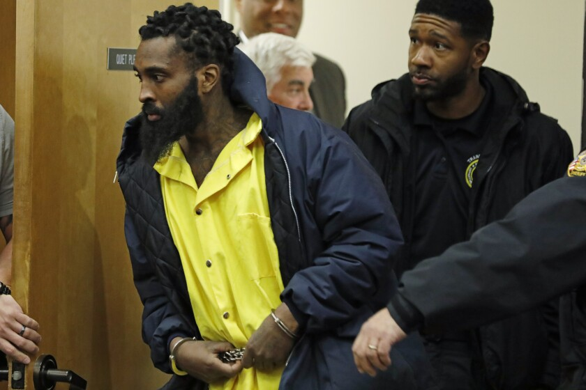 Marquis Flowers, 26, center, is directed by a lawman as he enters the Lincoln County Circuit Court, in Brookhaven, Miss., for his first appearance in state court since being indicted on capital murder charges of two policemen, Tuesday Nov. 12, 2019. Cpl. Zach Moak and Patrolman James White of the Brookhaven Police Department were shot to death Sept. 29, 2018. Flowers pleaded not guilty to the charges. (AP Photo/Rogelio V. Solis)
