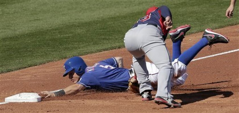 Texas Rangers' Ian Kinsler (5) beats the tag by Cleveland Indians shortstop Asdrubal Cabrera to advance to third on a single by Nelson Cruz during the second inning of an exhibition spring training baseball game, Thursday, Feb. 28, 2013, in Surprise, Ariz. (AP Photo/Charlie Riedel)