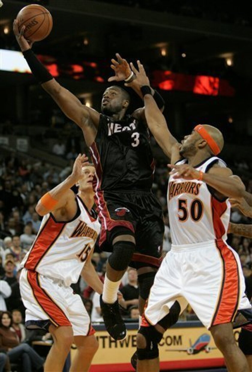 Miami Heat guard Dwyane Wade (3) scores past Golden State Warriors forward Corey Maggette (50) and Andris Biedrins, left, of Latvia, during the second half of an NBA basketball game in Oakland, Calif., Monday, Dec. 1, 2008. Miami won in overtime 130-129. (AP Photo/Marcio Jose Sanchez)