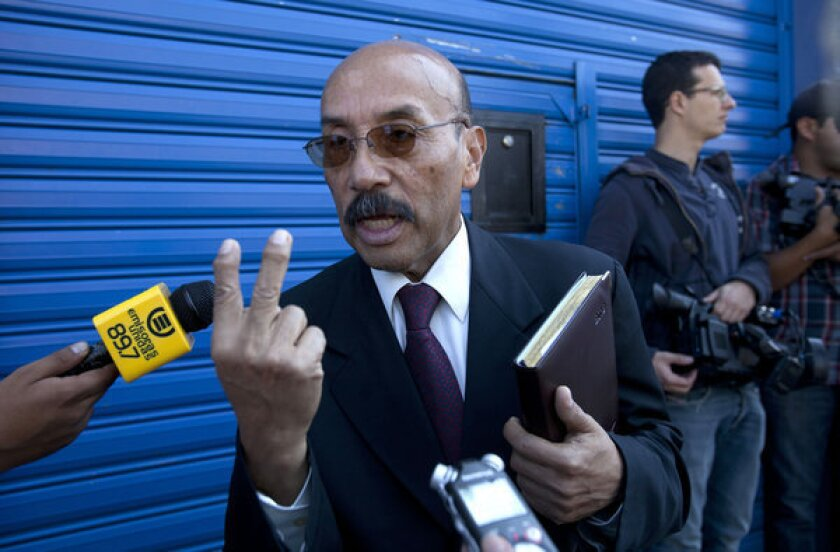 Telesforo Guerra, the lawyer for software company founder John McAfee, speaks Friday to journalists outside the detention center in Guatemala City where McAfee is being held.