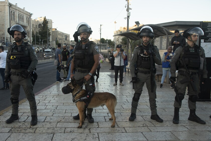 Israeli police and a police dog stand guard on the street.