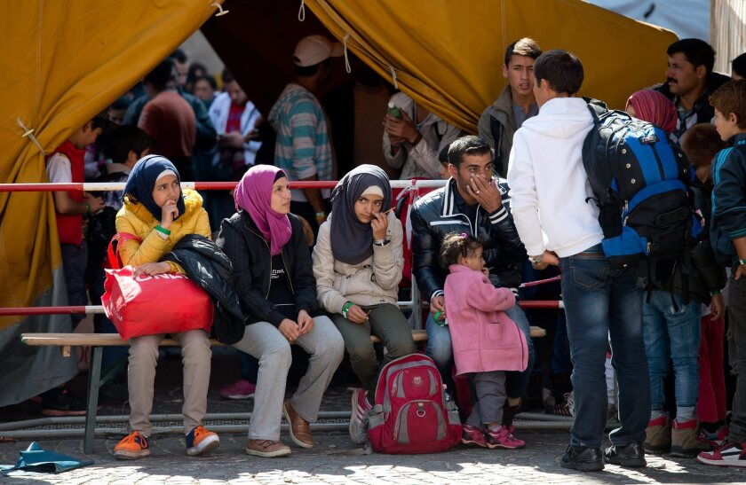 A group of refugees who had arrived earlier by train, waits to be transferred to a reception center from the central station in Munich, Germany, on Saturday.