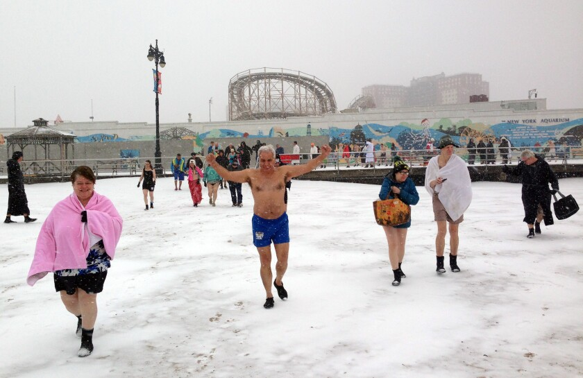 Louis Padilla, in blue swim trunks, and other members of the Coney Island Polar Bear Club in New York walk through the snow toward the water for their weekly winter swim. The 112-year-old club meets each Sunday from November until April for a dunk, which members swear is good for their health.