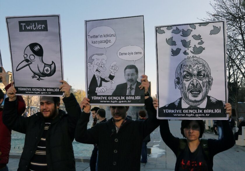 Members of the Turkish Youth Union hold cartoons depicting Turkey's Prime Minister Recept Tayyip Erdogan during a protest in Ankara against the ban on Twitter.
