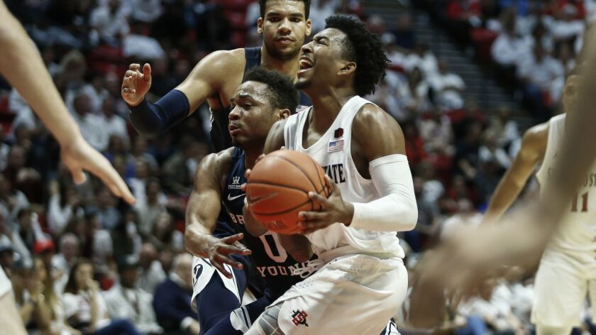 SDSU guard Devin Watson (0) drives to the basket under coverage from BYU guard Jahshire Hardnett (0) in the first half