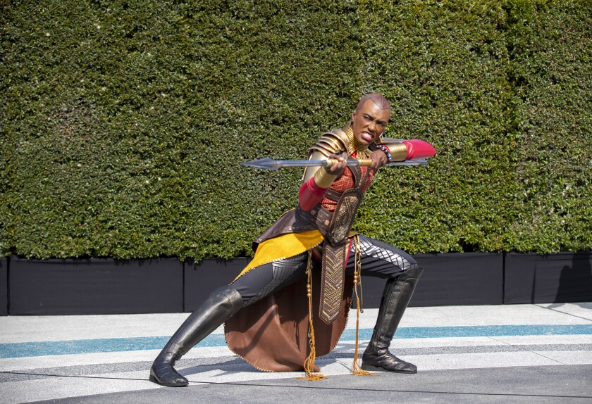 """A warrior in costume from the """"Black Panther"""" universe holds a spear in a fighter stance."""