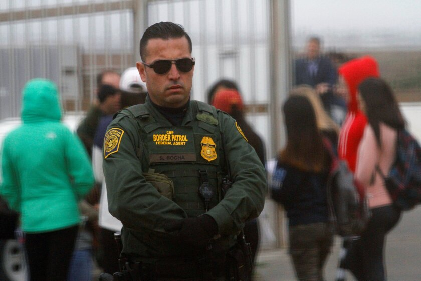 A U.S. Border Patrol agent looks on as people separated by immigration wait to see their relatives at an open gate on the fence along the Mexico and U.S border, as photographed from Tijuana.