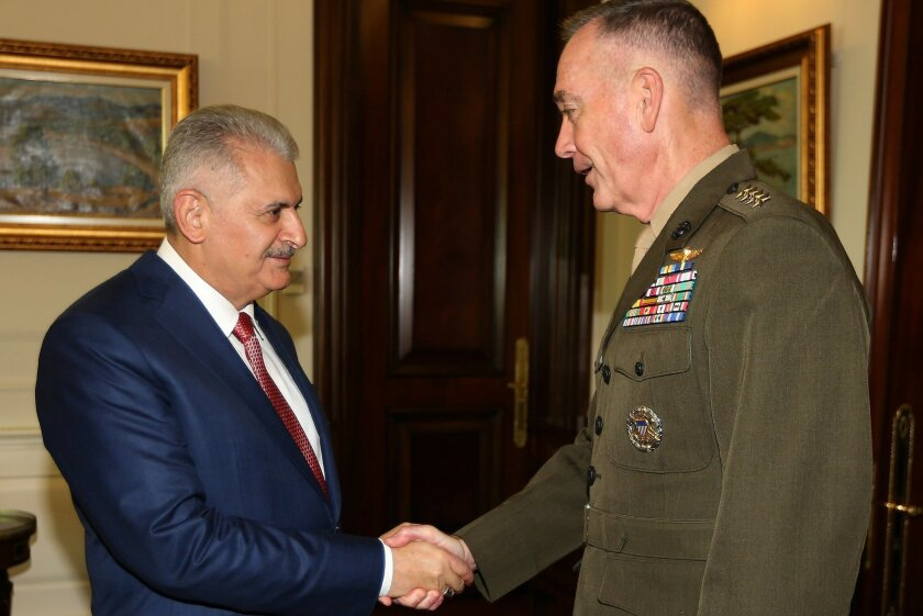 Turkey's Prime Minister Binali Yildirim, left, and The U.S. chairman of the Joint Chiefs of Staff, Gen. Joseph Dunford shake hands following a meeting in Ankara Turkey, on Monday, Aug. 1, 2016. Dunford visited U.S. military personnel stationed at Turkey's Incirlik air base Monday. He will later mee