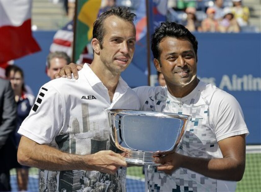 Radek Stepanek, of the Czech Republic, left, and Leander Paes, of India, hold the championship trophy after defeating Alexander Peya, of Austria, and Bruno Soares, of Brazil, in the men's doubles final of the 2013 U.S. Open tennis tournament, Sunday, Sept. 8, 2013, in New York. (AP Photo/Darron Cummings)