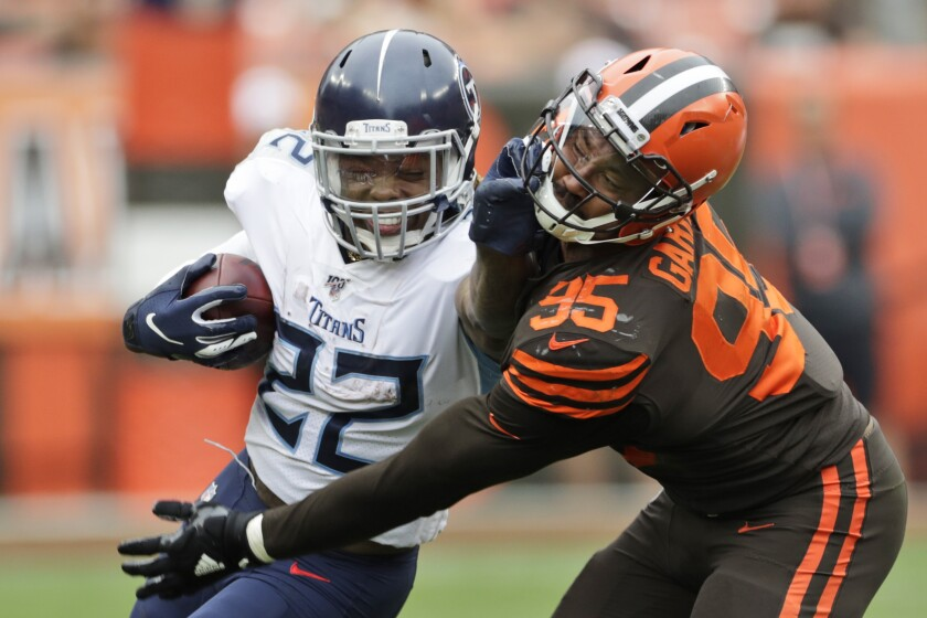 Titans running back Derrick Henry tries to power his way past Browns defensive end Myles Garrett during the second half Sunday.