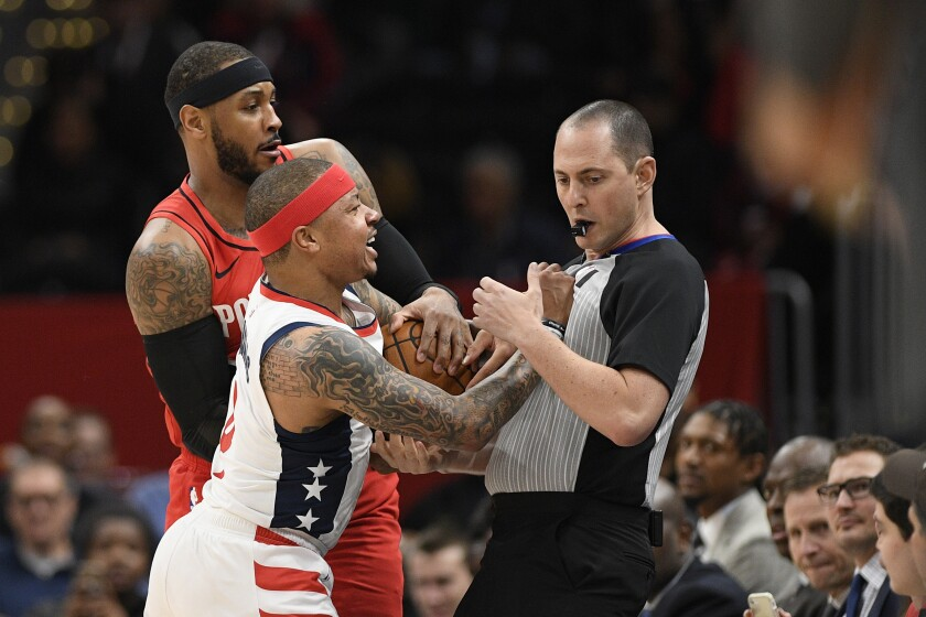Wizards guard Isaiah Thomas makes contact with referee Marat Kogut after getting tied up with Trail Blazers forward Carmelo Anthony and stumbling toward the sideline during a game Jan. 3, 2020, in Washington.